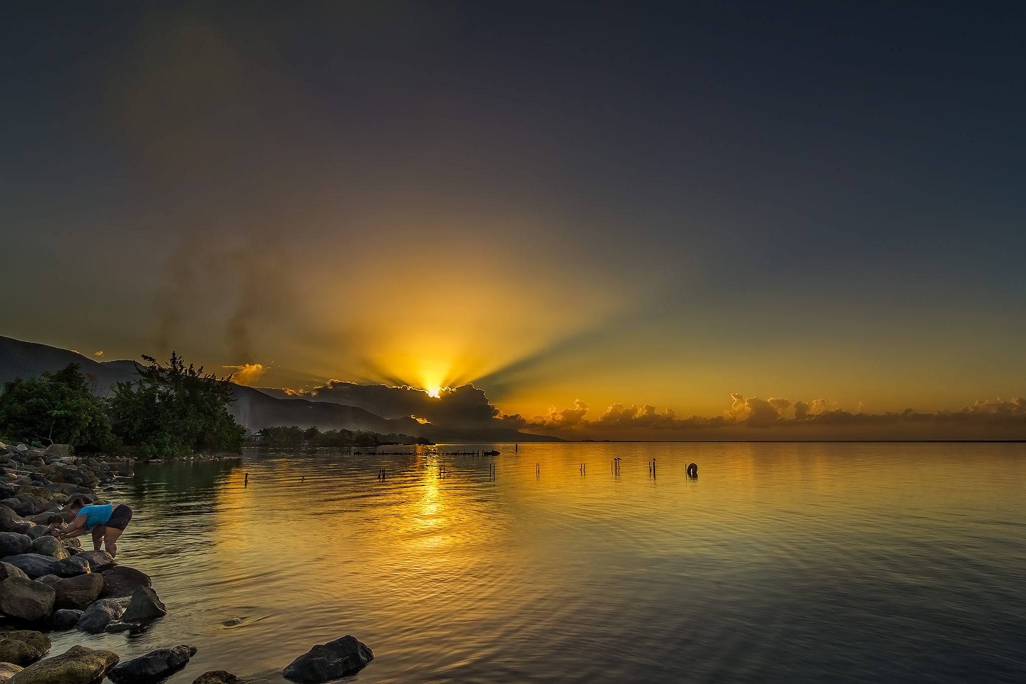 A mother gives her child a bath in the Caribbean Sea as the Sun rises in East Kingston, Jamaica.