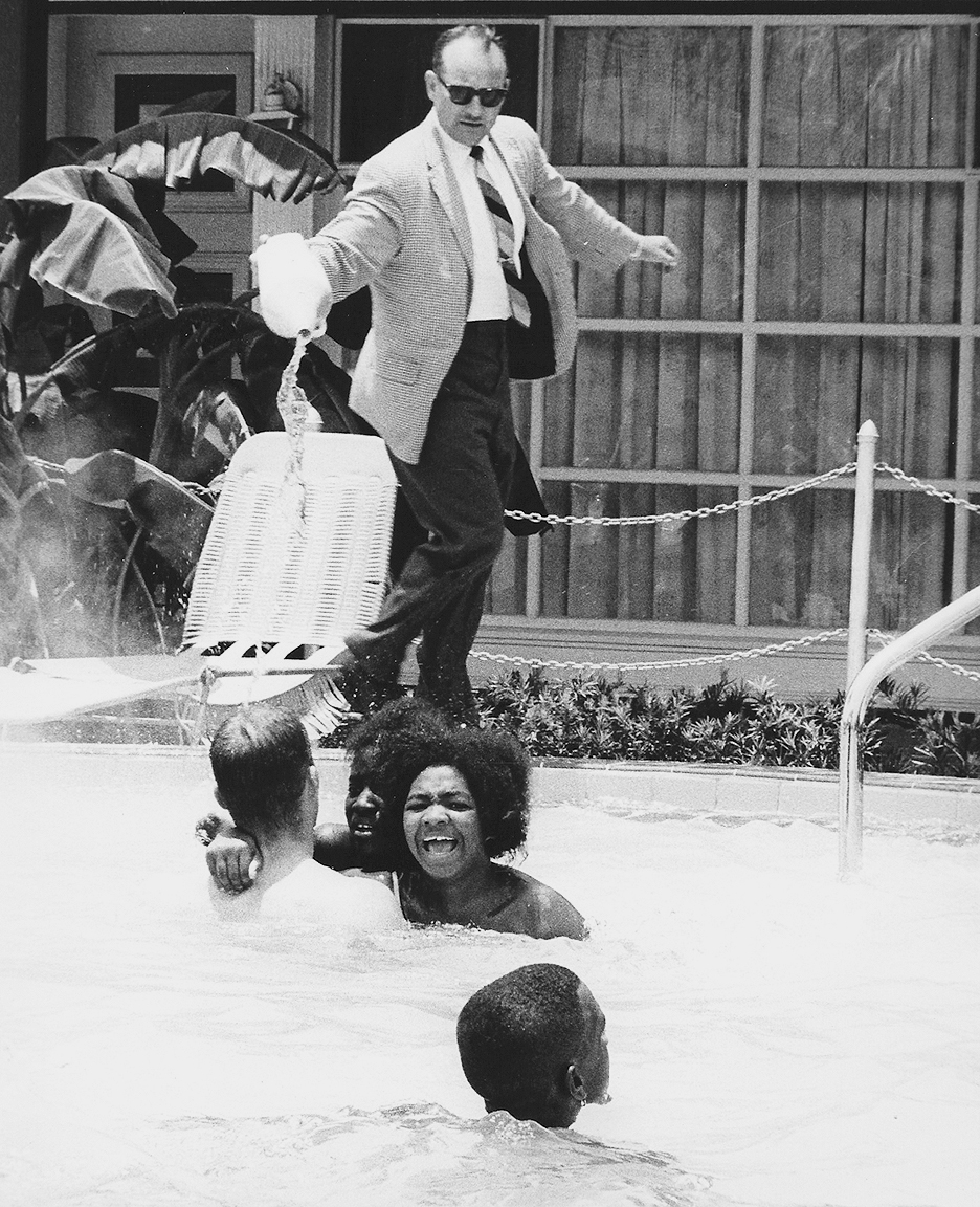 Monson Hotel owner, James Brock, pours muriatic acid in a swimming pool filled with black and white Civil Rights demonstrators. This photograph helped break the filibuster in the Senate, allowing the passage of the 1964 Civil Rights Act.