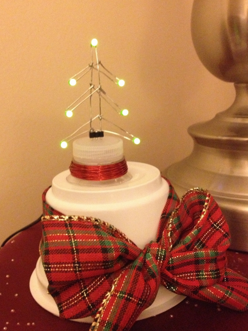 Wirelessly-lit LED Christmas tree on its base.
