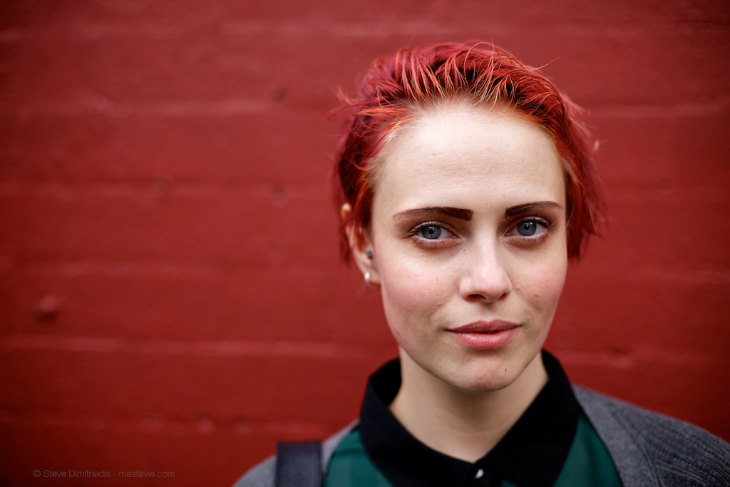 Street Portrait of a woman against a red wall, Haymarket in Sydney | 50mm lens | 2014