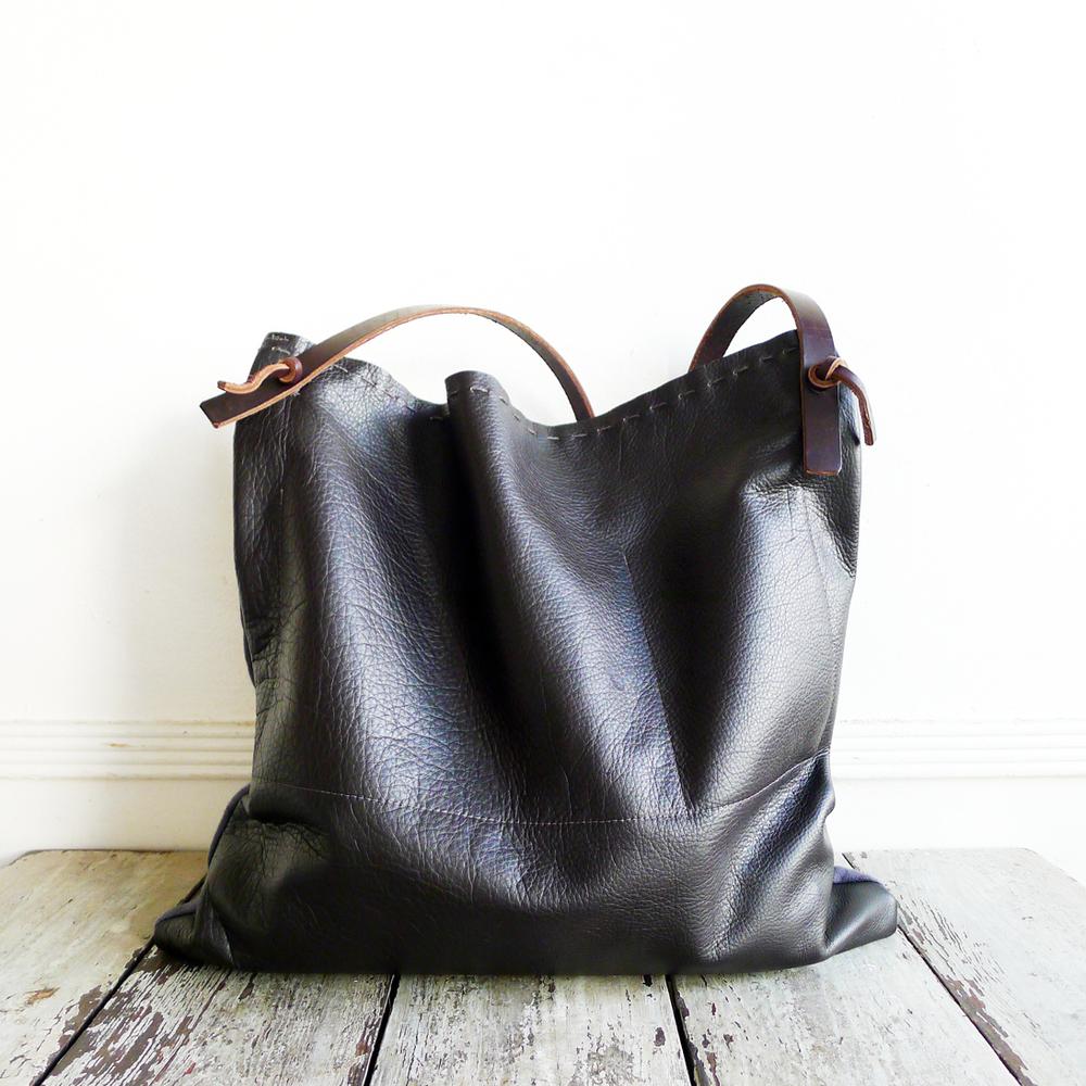 leather back. interior pocket. hand stitched detail top of bag