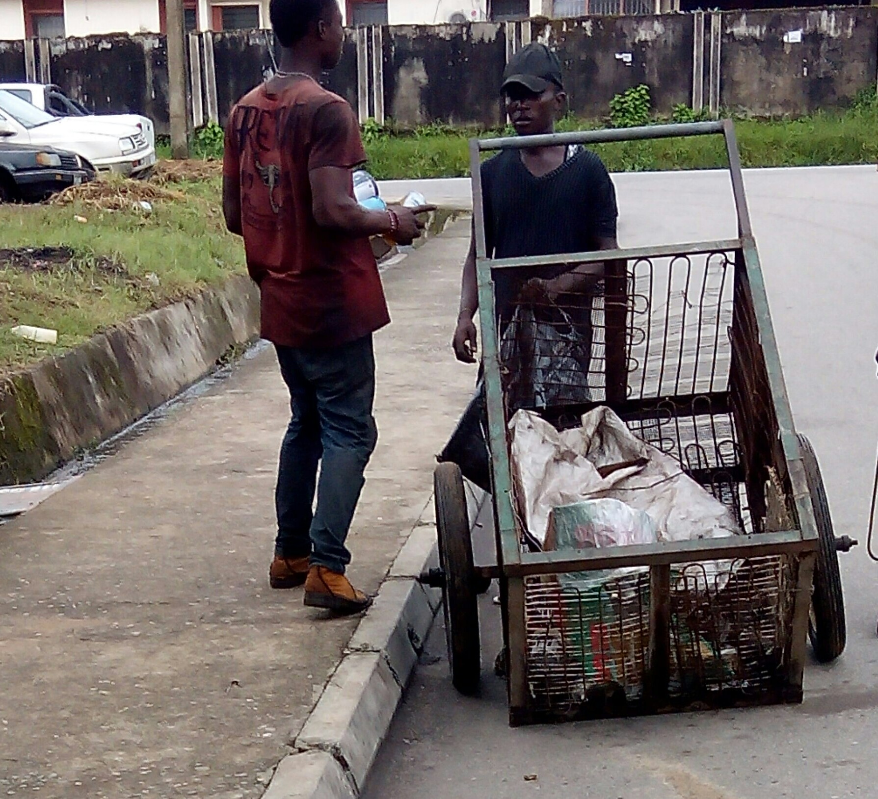 Daniel with his cart, being offered empty cans.