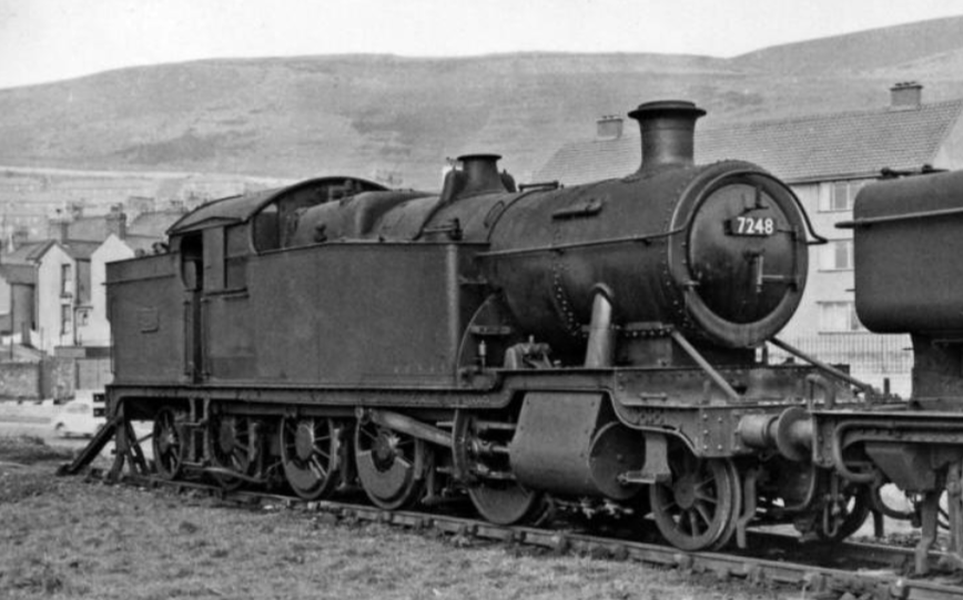 7248, an ex-GWR 2-8-2 tank, in the north side sidings of Swansea East Dock, circa 1955. Kilvey Hill is in the background. © Ben Brookbank and used under Creative Commons licence.