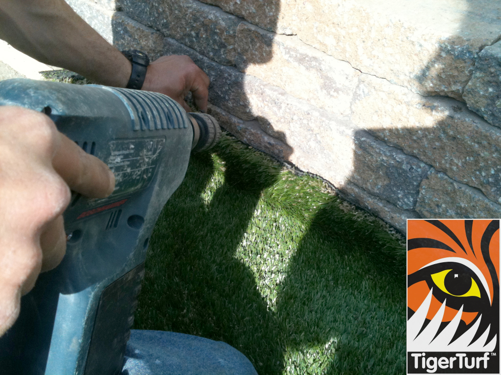 installer using screwgun to secure turf