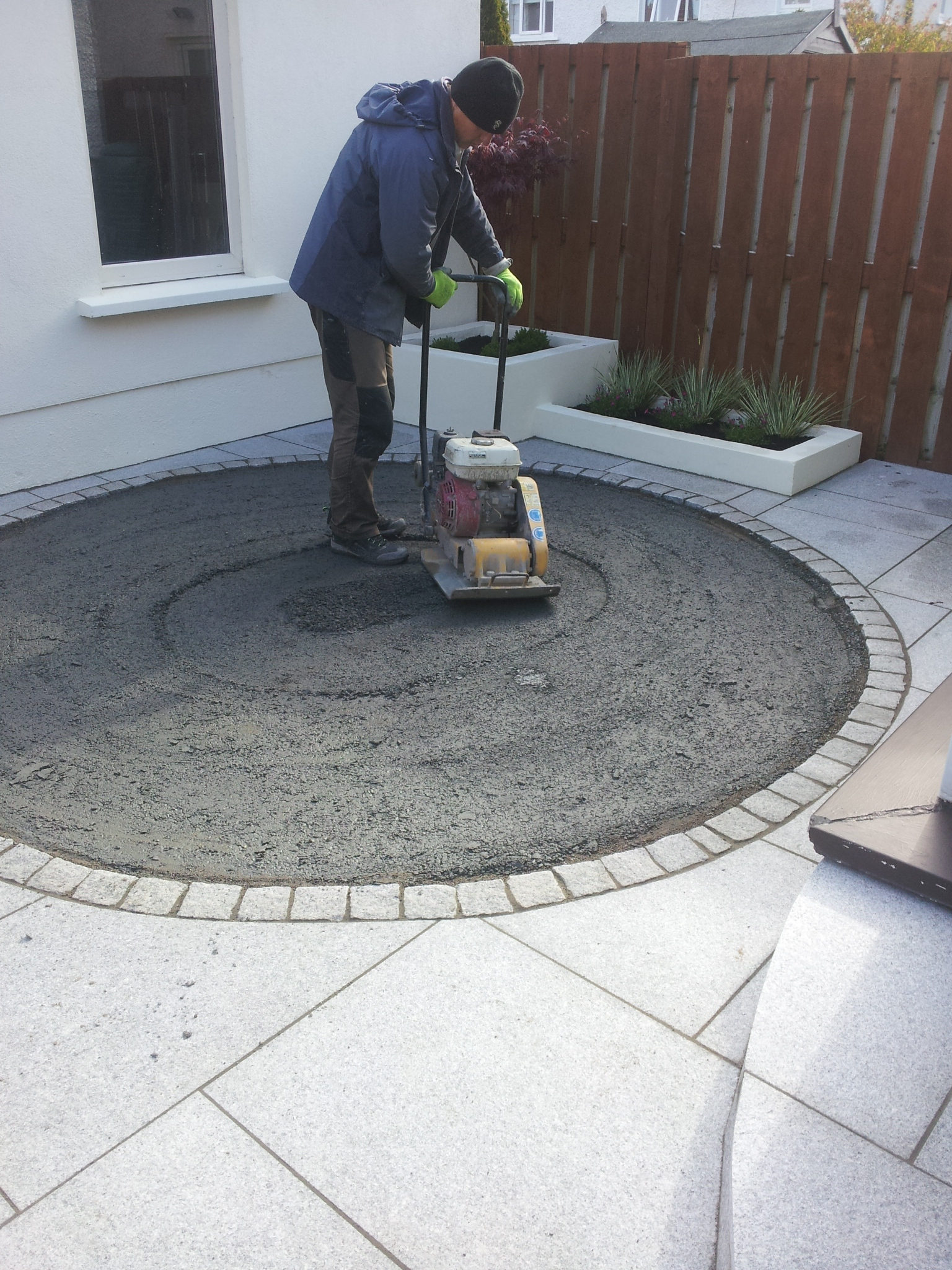 installer compacting base material for grass