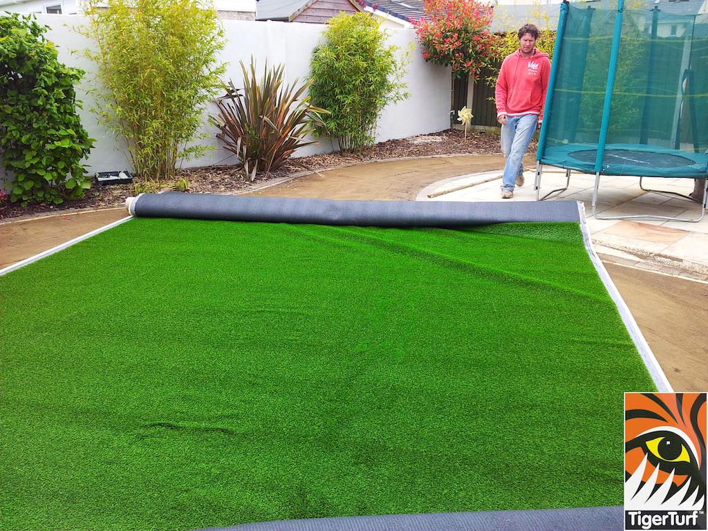 installer fitting grass around trampoline