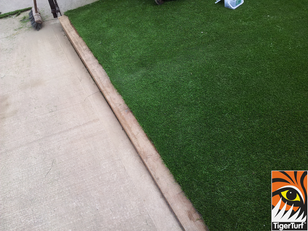 new synthetic lawn beside driveway