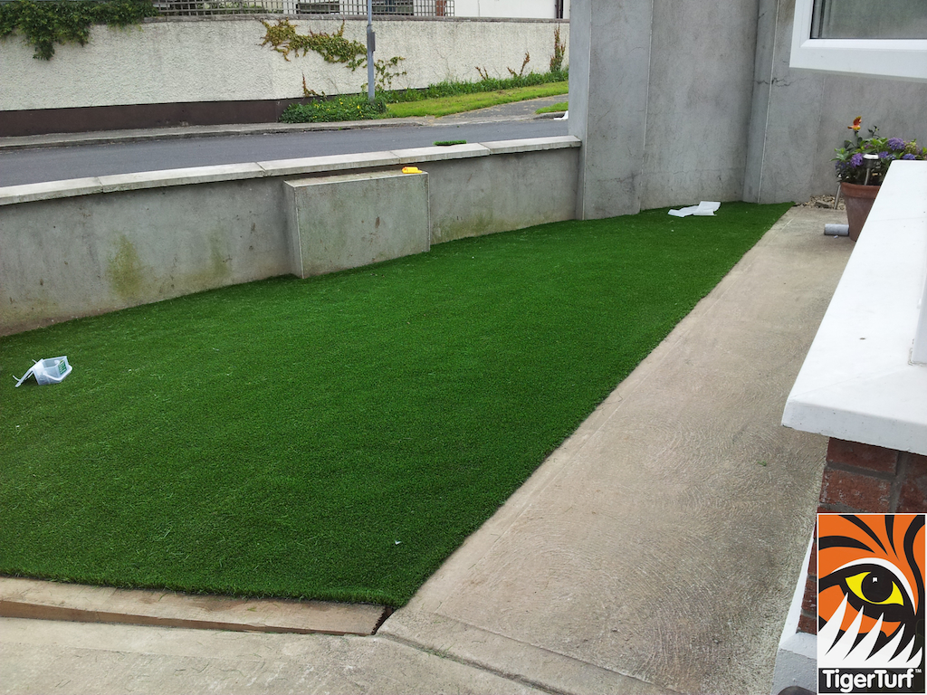 new synthetic lawn installed beside driveway