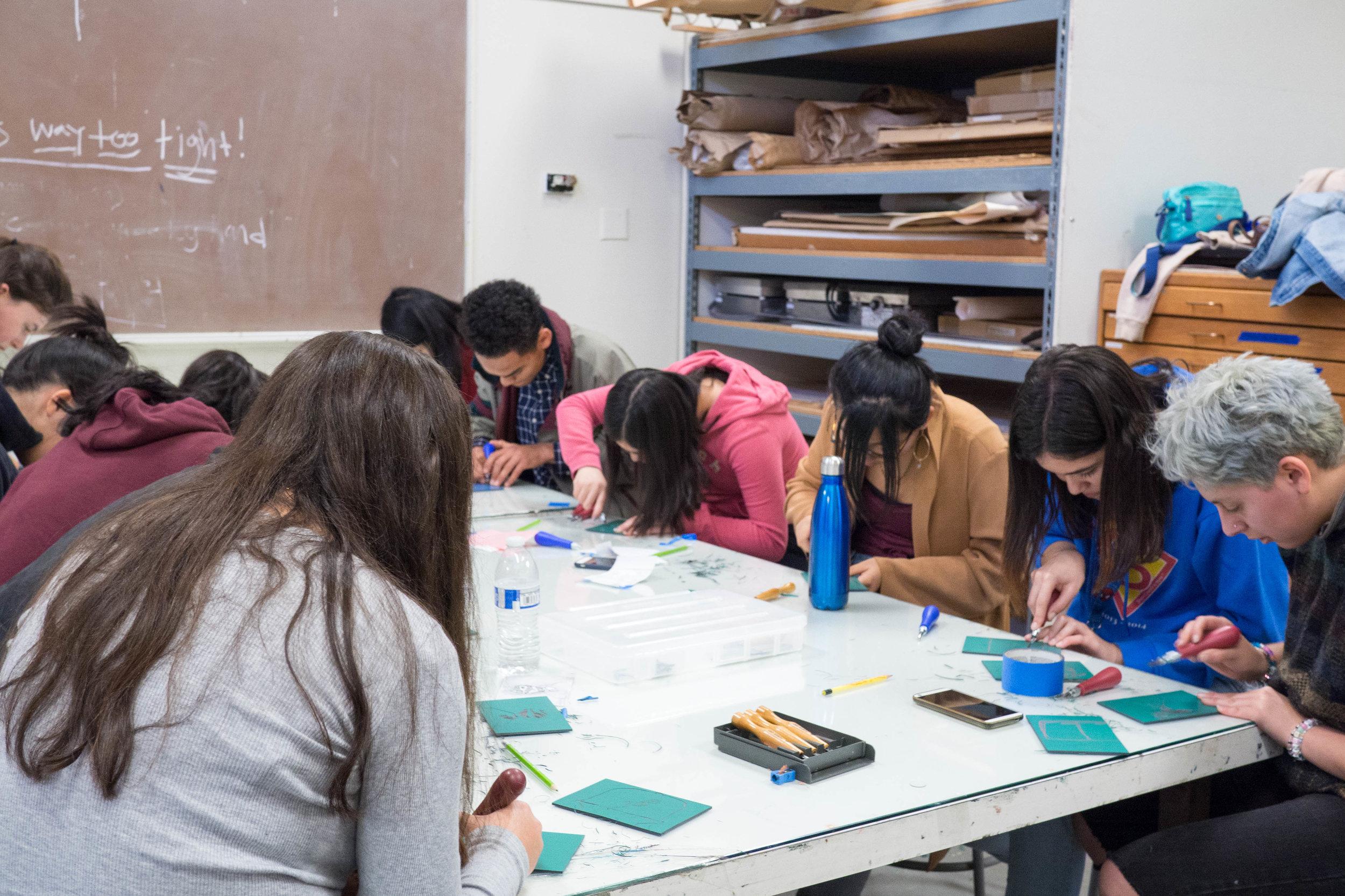 Participants carve their blocks as a group