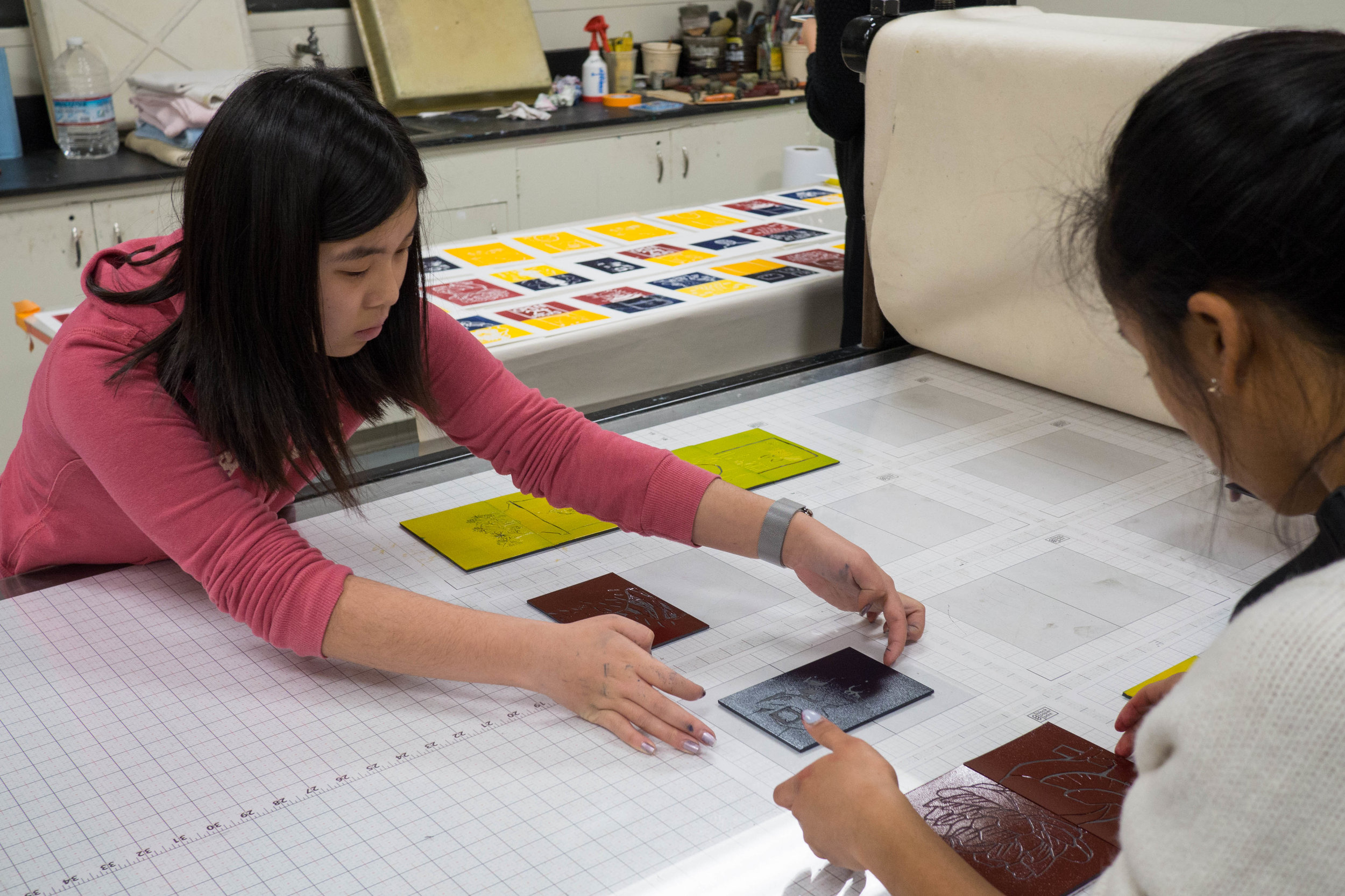 Participants ink blocks and place them on the etching press for printing