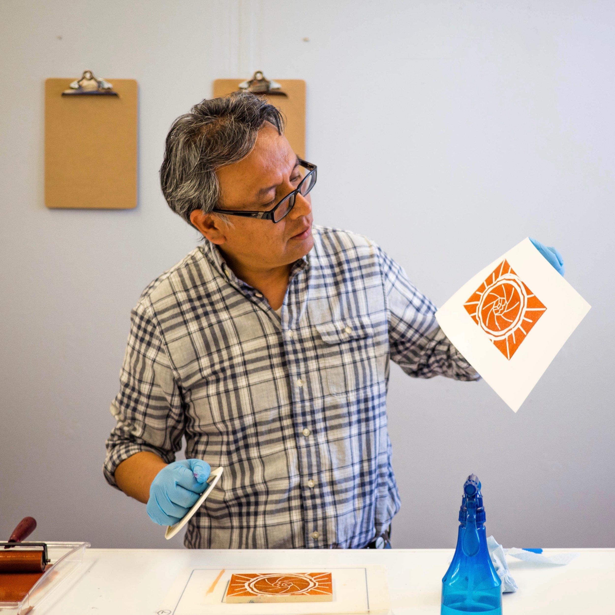 Raphel pulls his first print using hand pressure