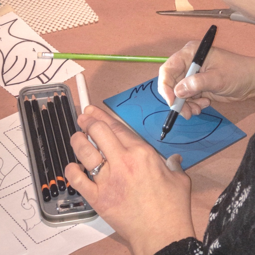 A participant reinforces her drawing with sharpie as she finalizes her design.