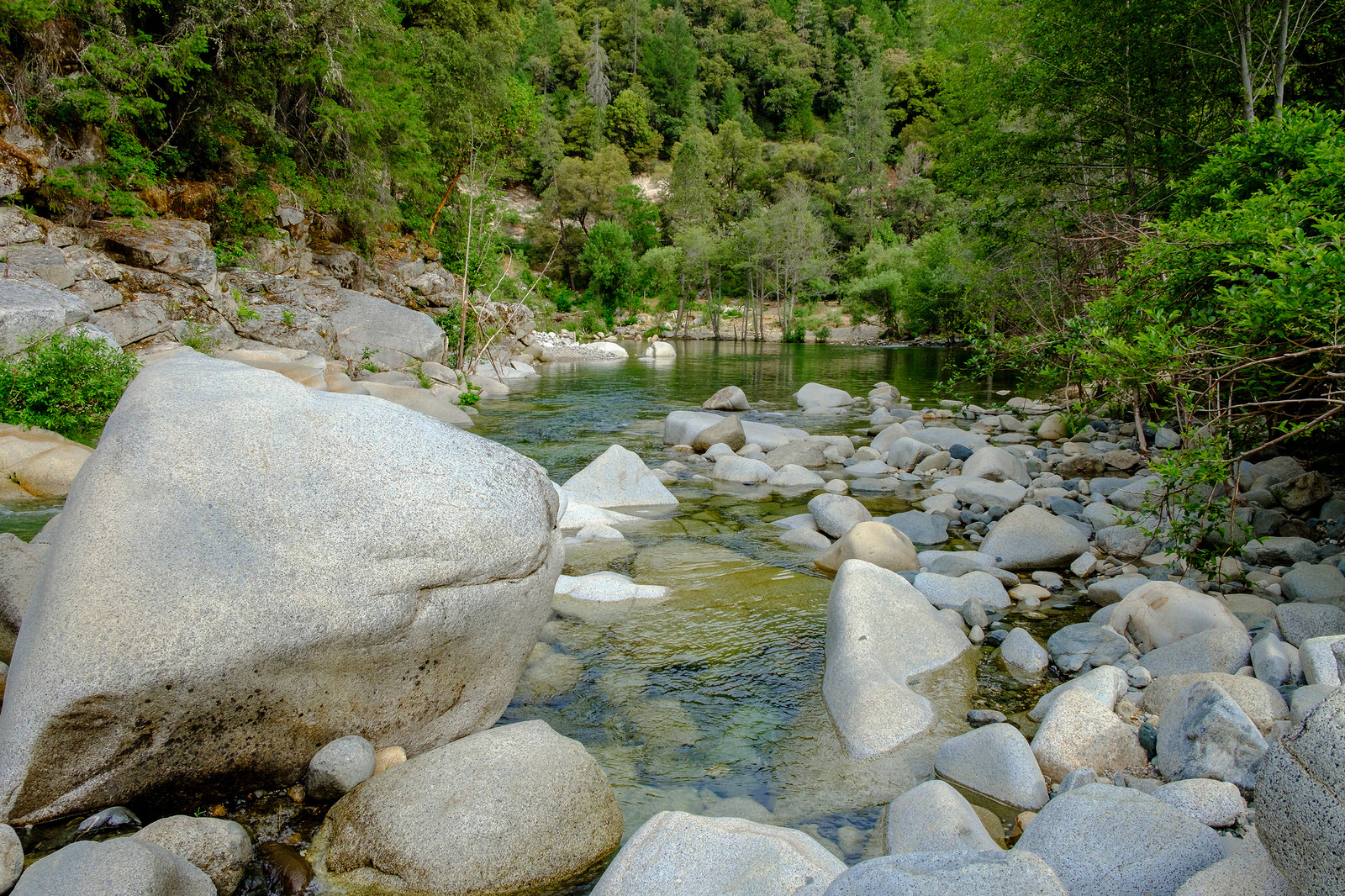 When you cross the bridge, you will find a large parking lot with bathrooms, park tables and a sandy beach that gives you access to this large open section of the river. You can swim and even use the rope swing.