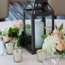 Lanterns with mounded flowers on one half of your tables