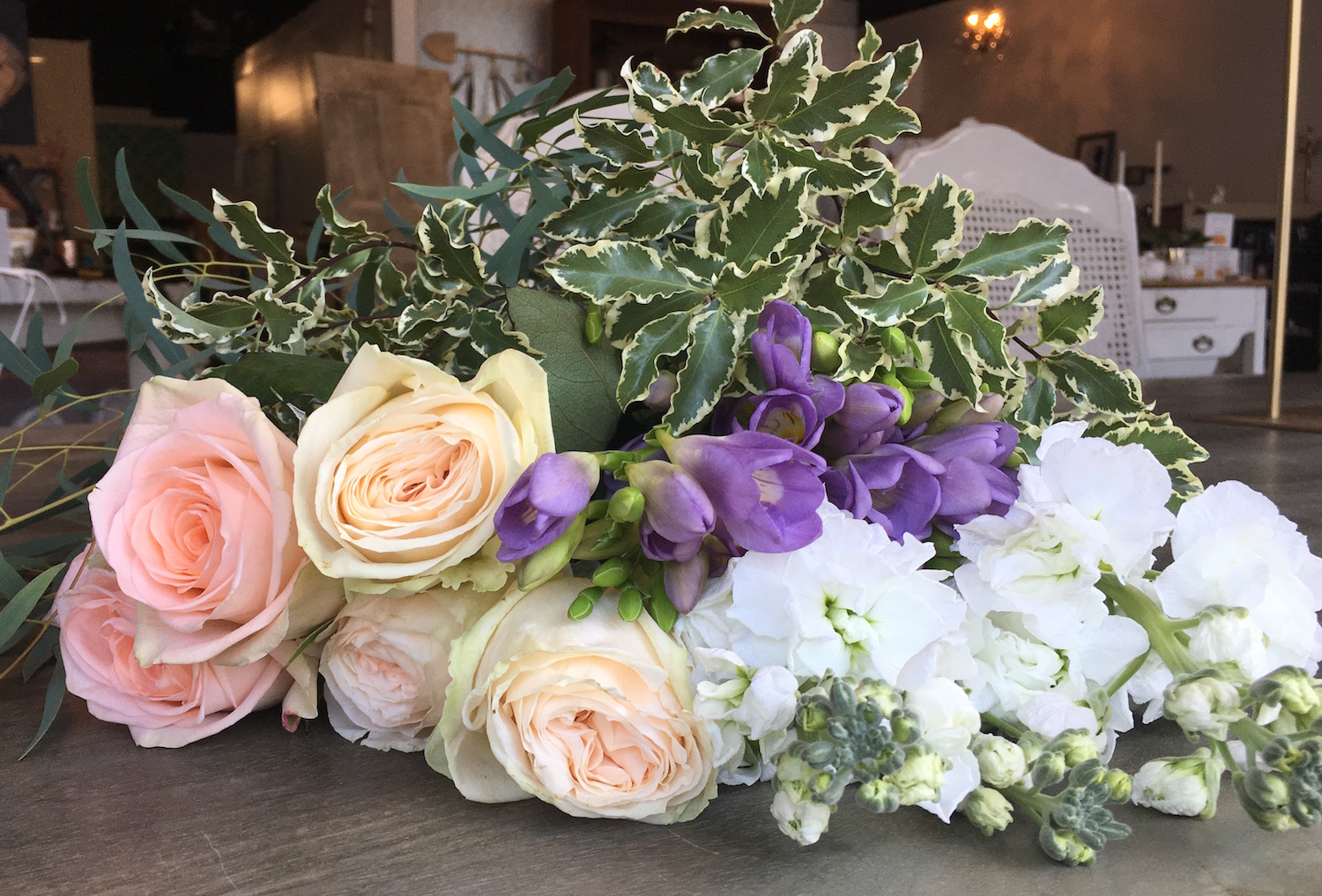 From left to right: Peach roses, cream Garden Roses, purple Freesia, white Stock. On top Feathered Eucalyptus and Variegated Pittosporum.