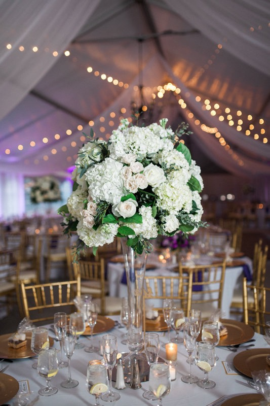 Each vase and votive must be cleared away, a service that your florist will provide. Gorgeous tall centerpiece in pilsner vase at Rust Manor House in Leesburg. Photography by Birds of a Feather.