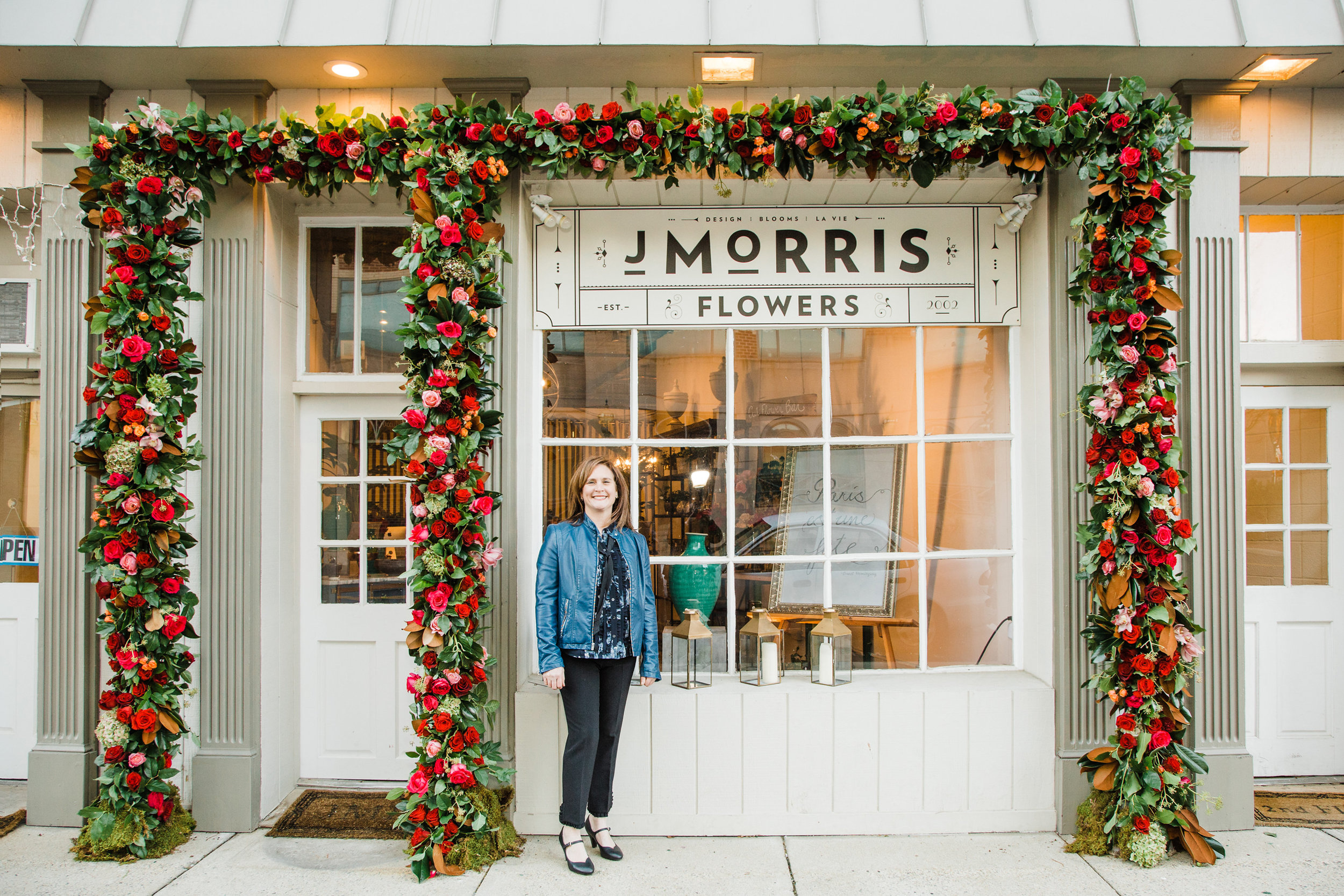 Jennifer Morris, Owner and Director of Blooms for J. Morris Flowers, 120 East Market Street. Ruby Red, Burgundy and burnt Orange strike a balance with blush pink and greens. This installation was a team effort under the direction of Jennifer, inspired by installations seen on the streets of London.