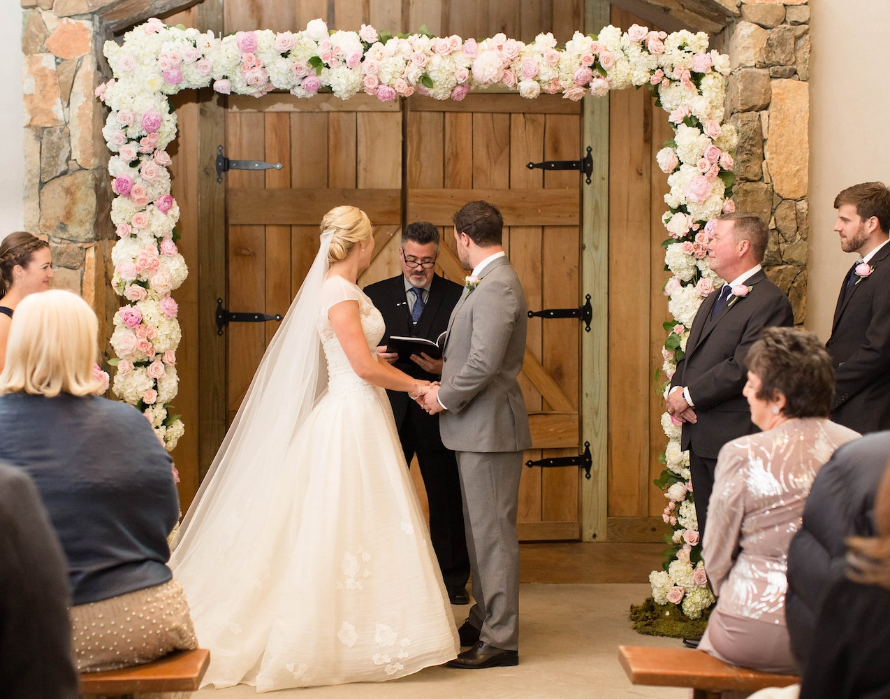 Stone Tower Wedding with full floral arch. Photography by Candice Adelle.