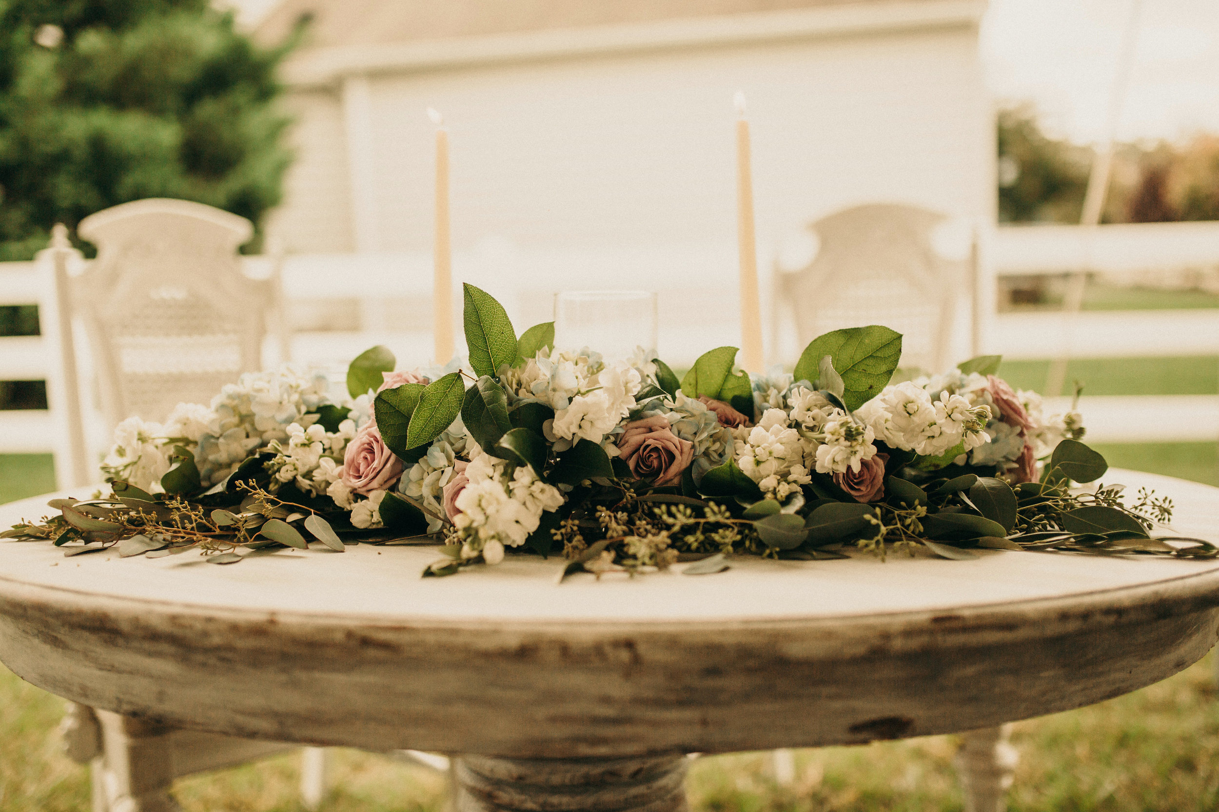 Florals and greens for a Sweetheart table with Seeded Eucalyptus, Salal, Stock, Hydrangea and Roses. Photography by Olivia Markle.