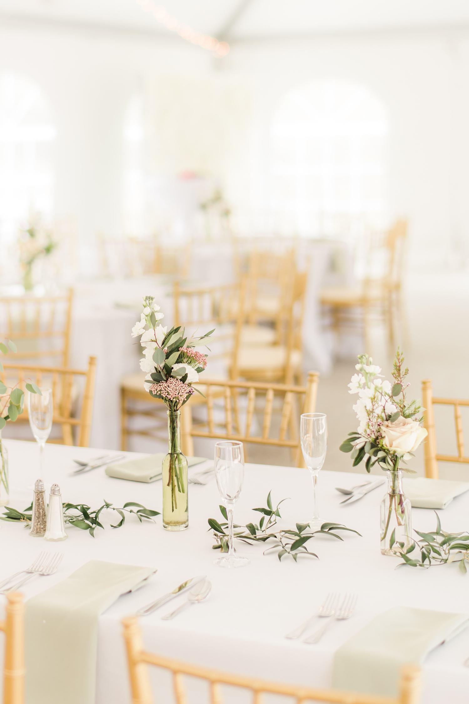 Long tables at Rust Manor House with loose greenery and bud vases. Photography by Stephanie Messick.