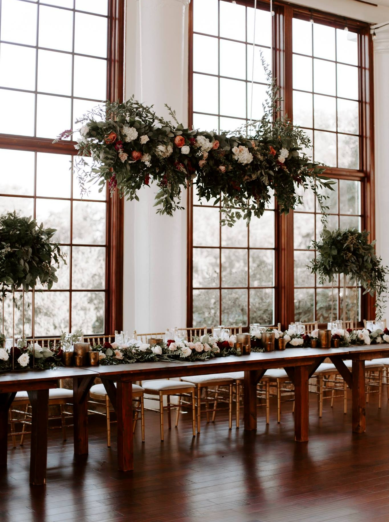 King's table at Raspberry Plain Manor photographed by    We Are the Cashmans   . Tall centerpieces with greenery flank the long table with a raised floral design overhead. Floral garland and bridesmaids bouquets with groupings of votive candles.