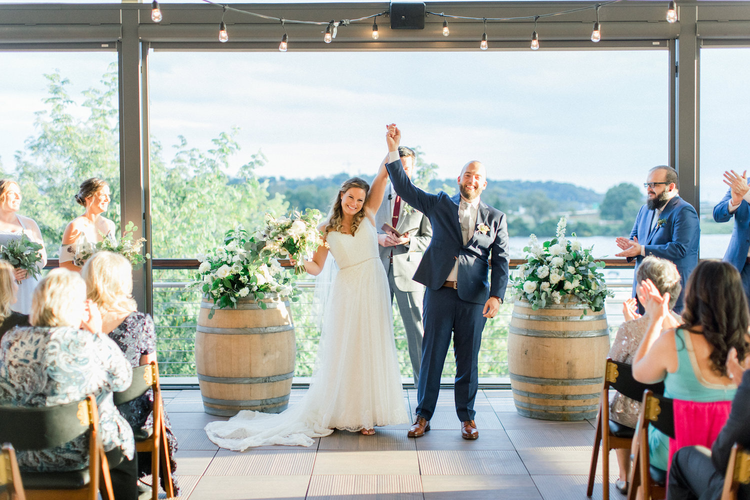 A view of the Anacostia River awaits wedding couples at    District Winery    in Washington, DC. White and ivory flowers with loose and flirty greens flank the officiant. Image by Abby Grace Photography.