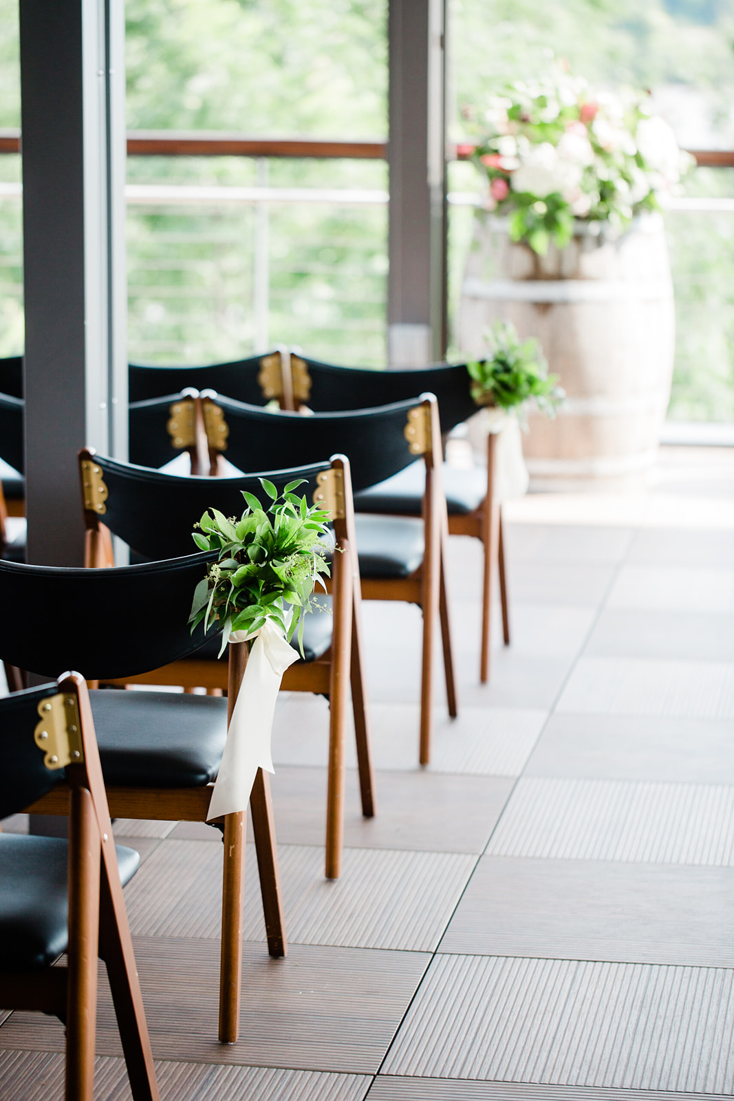 Greenery only chair bundles with ribbon at District Winery in Washington DC. These can be repurposed at your cocktail hour, on a bar or in a lounge. Image by Susie and Becky Photography.