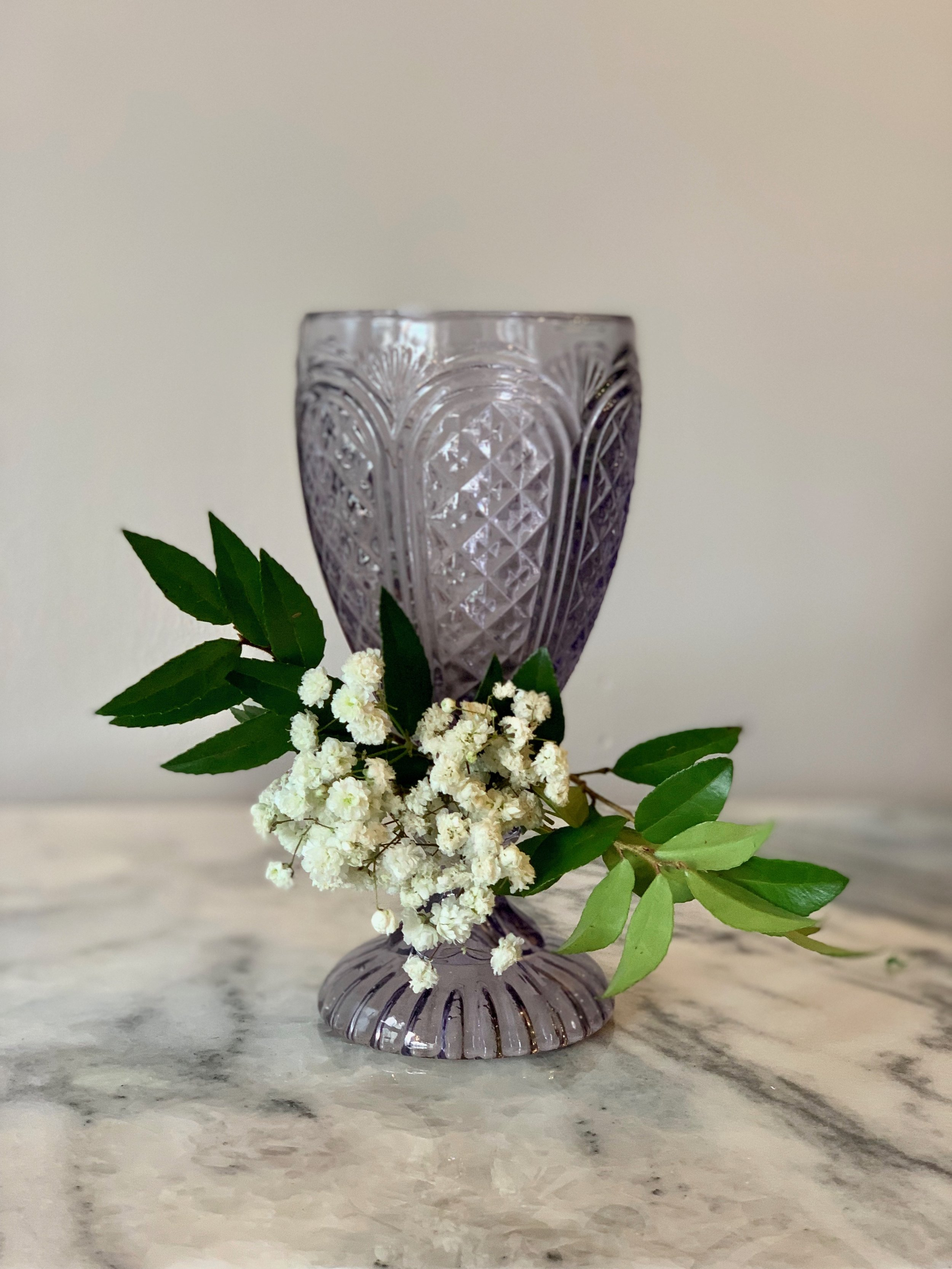 Wine glass with Babies Breath and greenery.