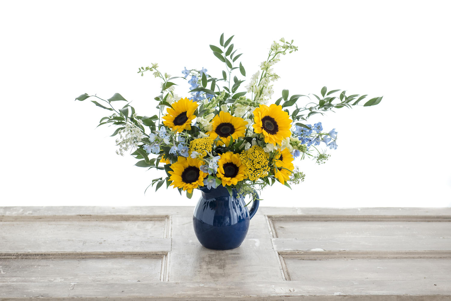 Sunflowers and Delphinium explode out of this blue pitcher vase with greens and Yarrow to complement.