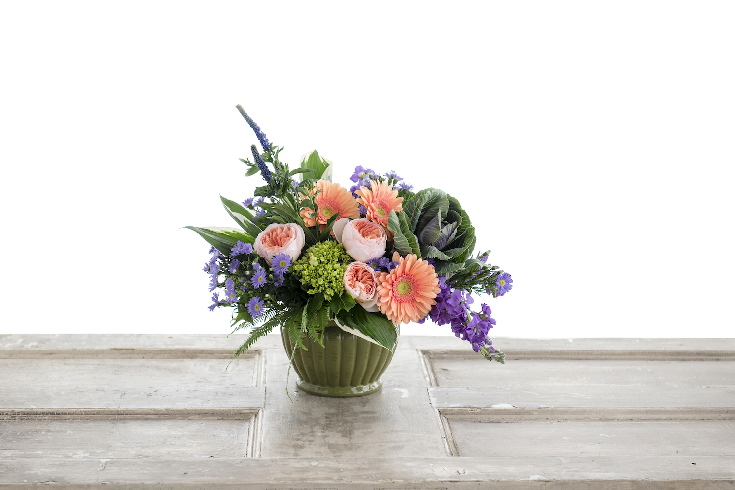 Purple and peach combine in the sage green pot with a lovely design. This is part of the Artisan Collection at J. Morris Flowers.