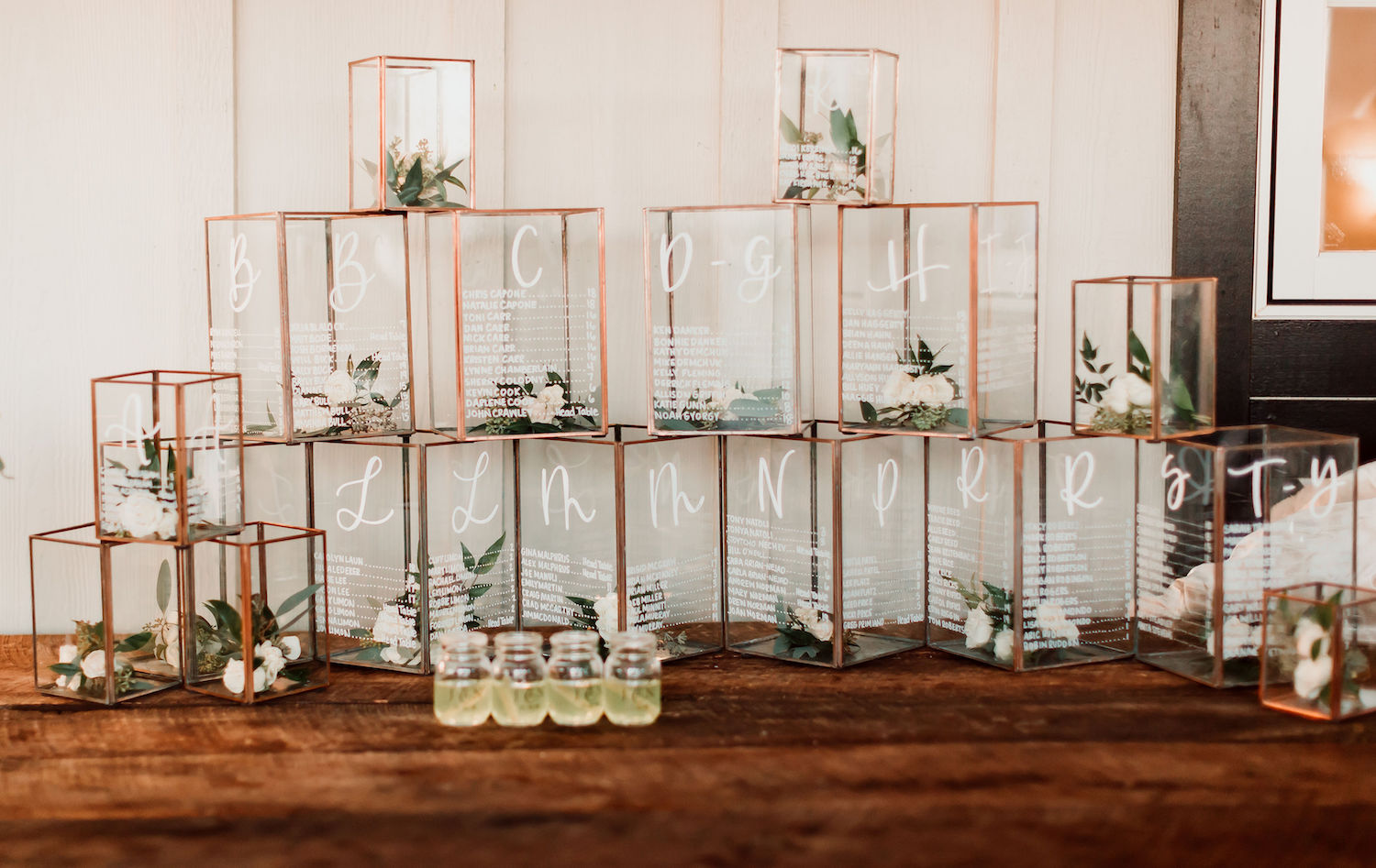Jami, the bride, used these copper and glass lanterns with the names of their guests and table assignment etched into the glass. We added Ivory Spray Rose and a mix of greens and voila - flowers everywhere. Photography by Hay Alexandra. Table at Shadow Creek in Purcelleville, Virginia.