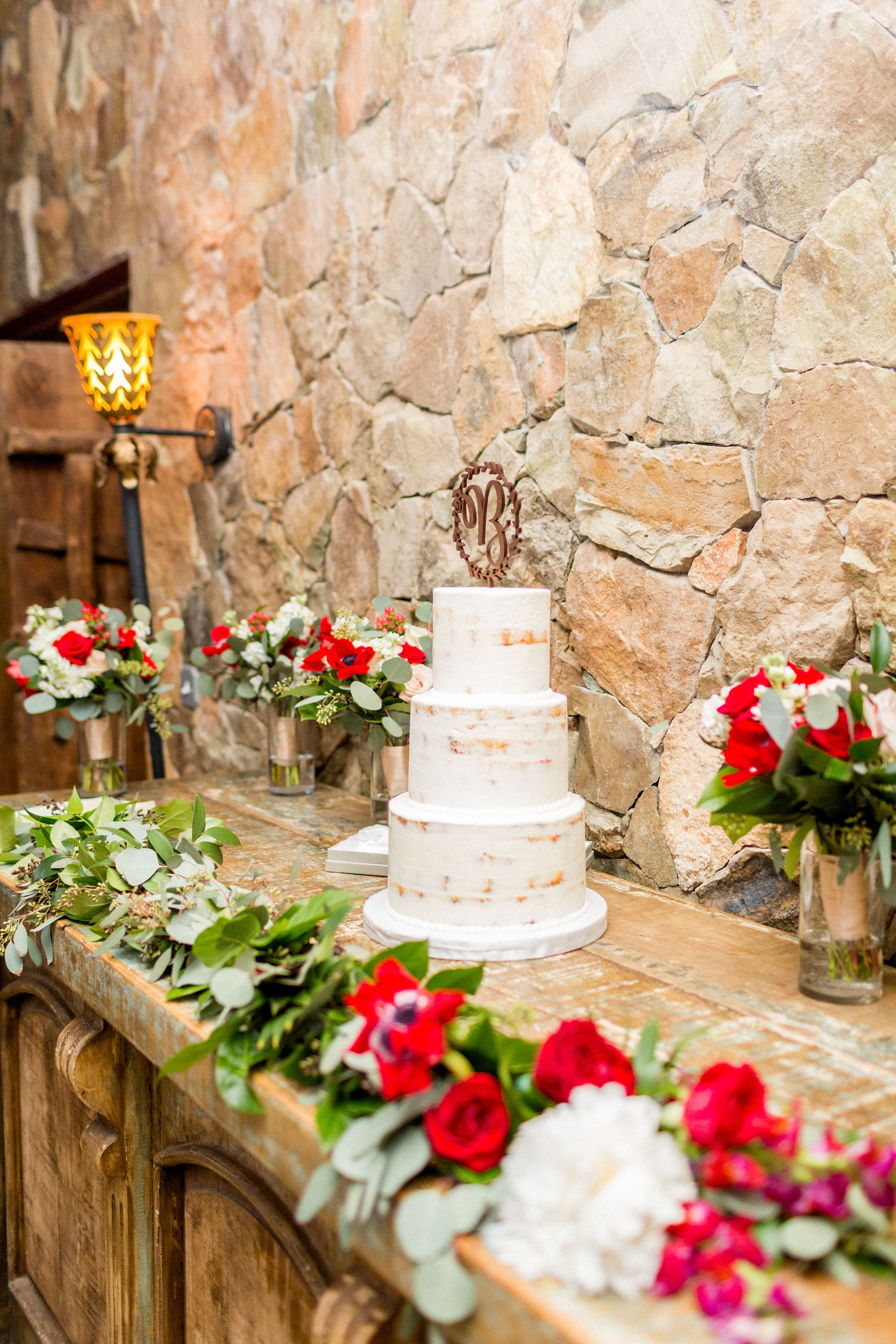 Greenery blends to flowers in this mantle spray at Stone Tower Winery. The cake was surrounded by bridal bouquets in cylinders. Photography by Candice Adele.