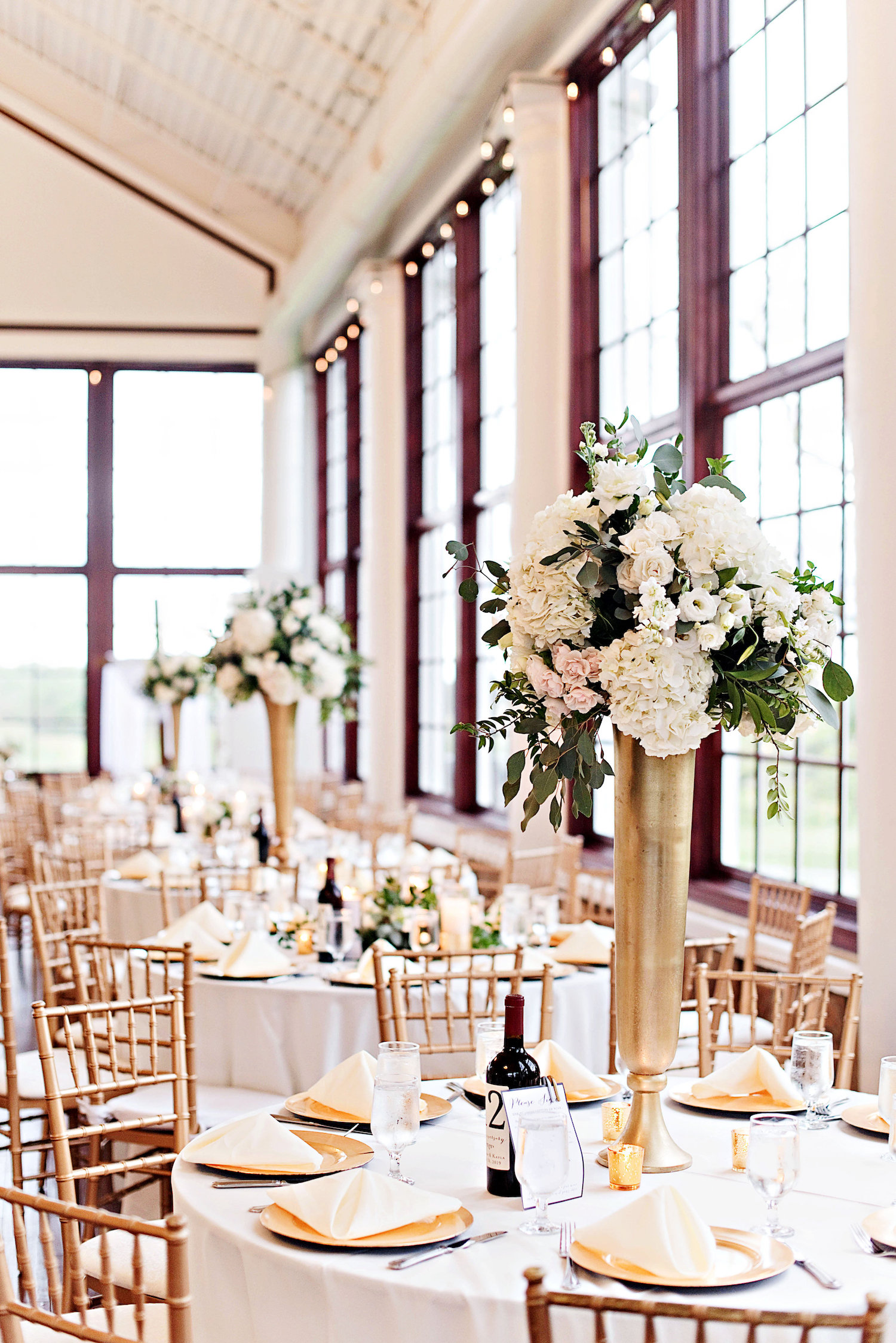 The-Photography-Smiths-Tall-Centerpieces-Gold-Pilsner-white-flowers-greenery.jpg