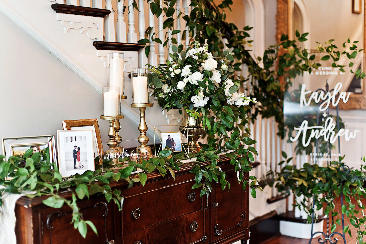 The entryway table, stairwell and welcome sign with greens and floral included personal framed photos.