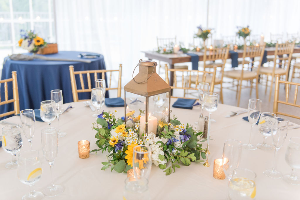 A second centerpiece option included Sunflowers and Delphinium in a wreath around this gold lantern. Photography by Emily Alyssa Photography at Rust Manor House.