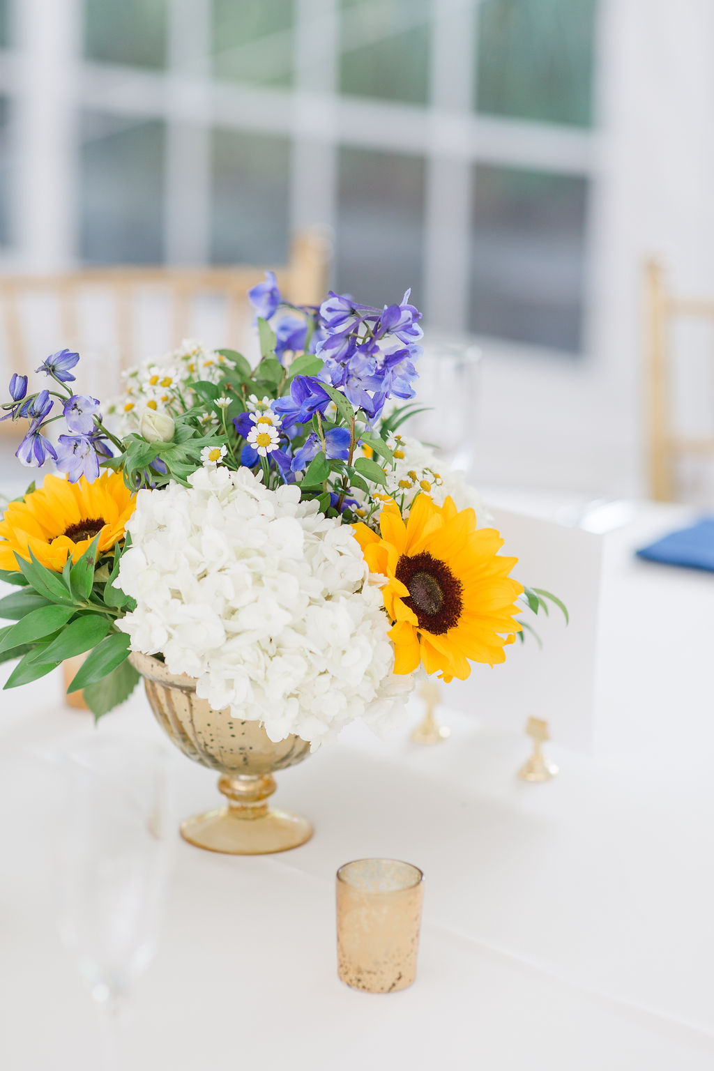 Centerpieces in an elegant gold compote with Sunflower and Delphinium for the blue in this couple's palette. Photography by Emily Alyssa Photography.