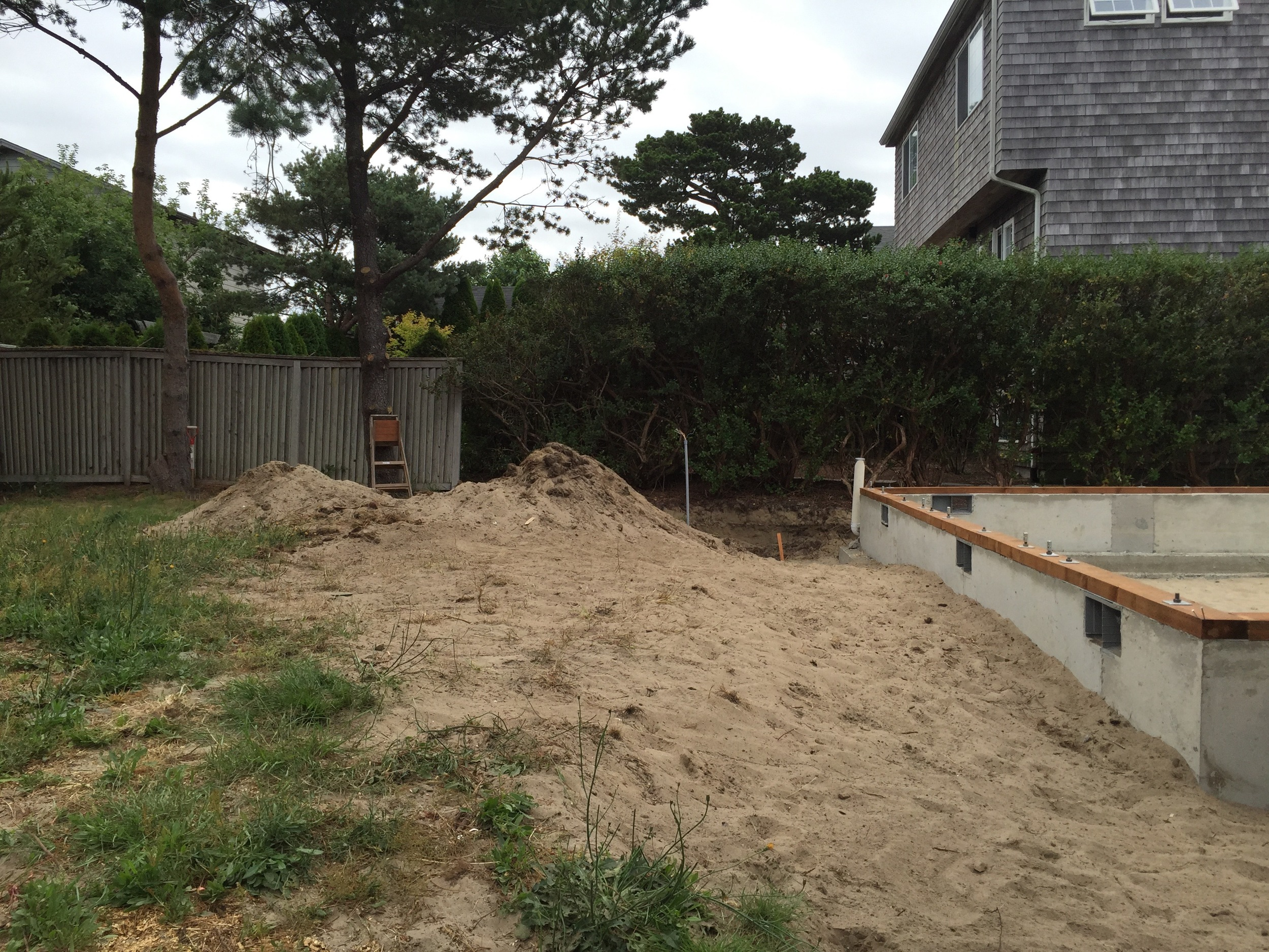The results of myfirst day's work -- moving this heap of sand back in,around the foundation