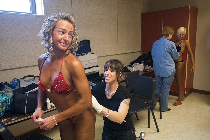 On the day of the competition, Lauren's friend and assistant, Jessa English- a past-winner of the competition, makes last-minute adjustments to Lauren's wardrobe and rubs tanning lotion on Lauren backstage.