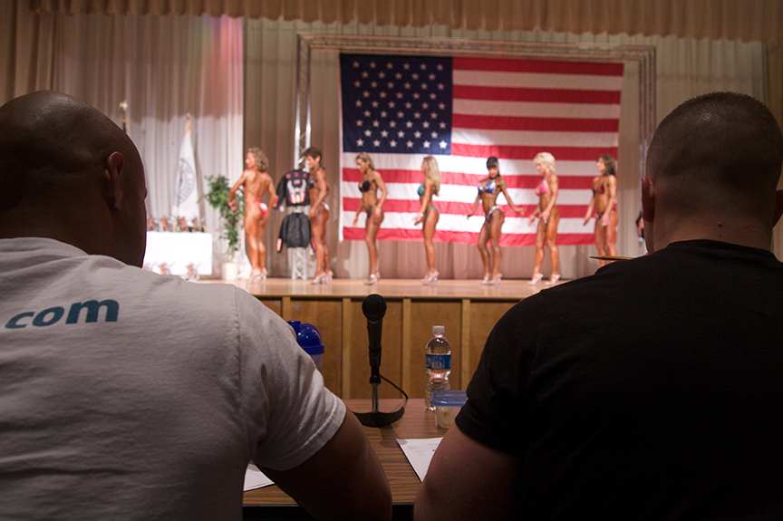 Judges examine the contestants for symmetry, definition, and figure, as shouts of support erupt from the audience.