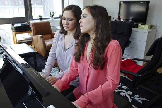 Twin sisters Michelle and Christina Naughton rehearse in their Upper West Side apartment. They perform in Central Park on Tuesday. Steve Remich for The Wall Street Journal