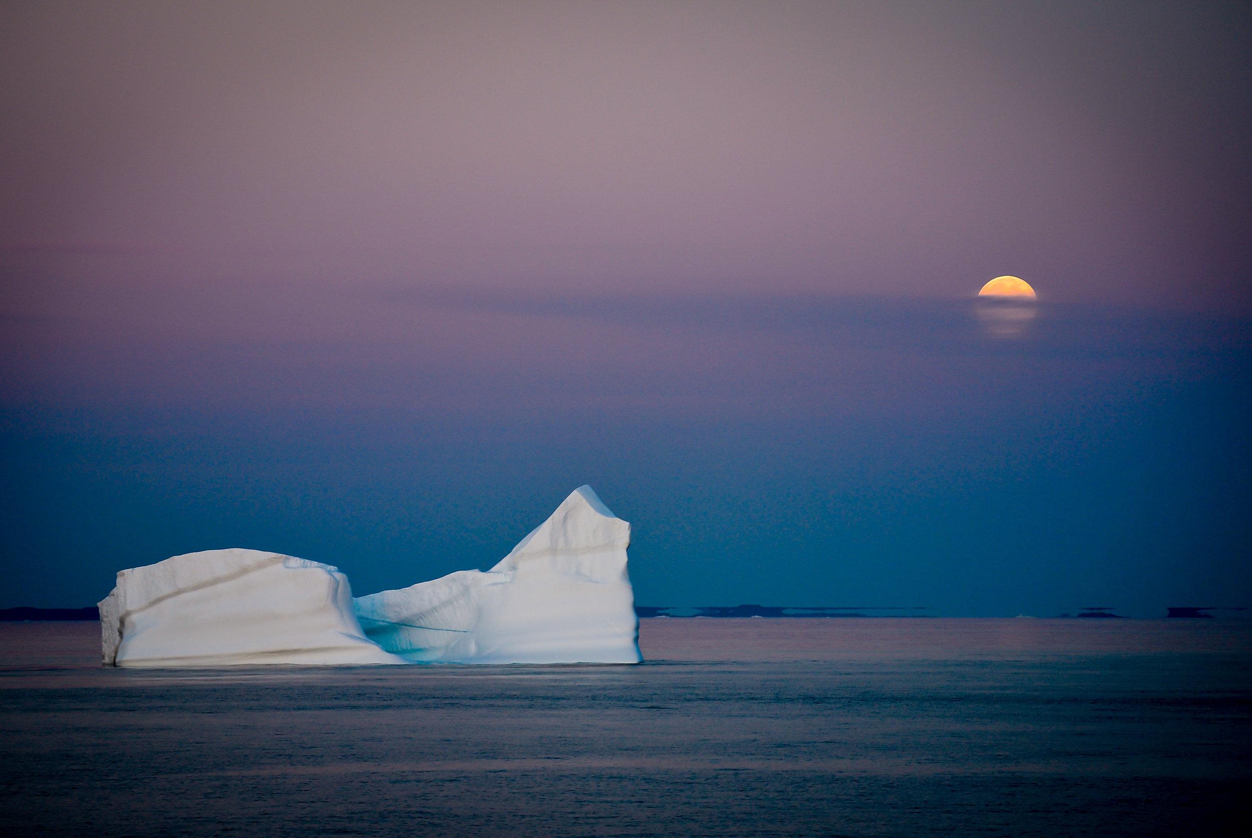 Iceberg and full moon off the coast of Greenland