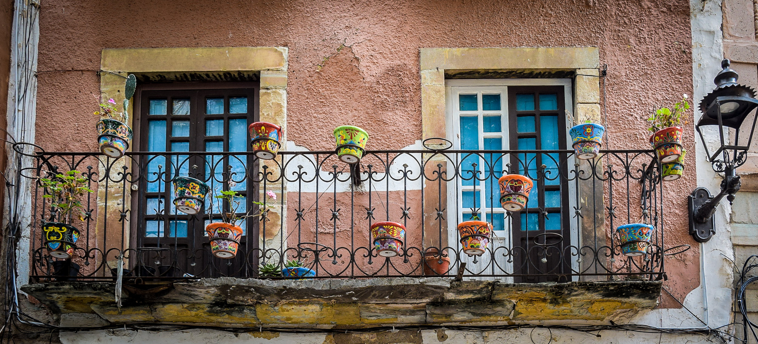 Colorful flowerpots on a balcony in Guanajuato