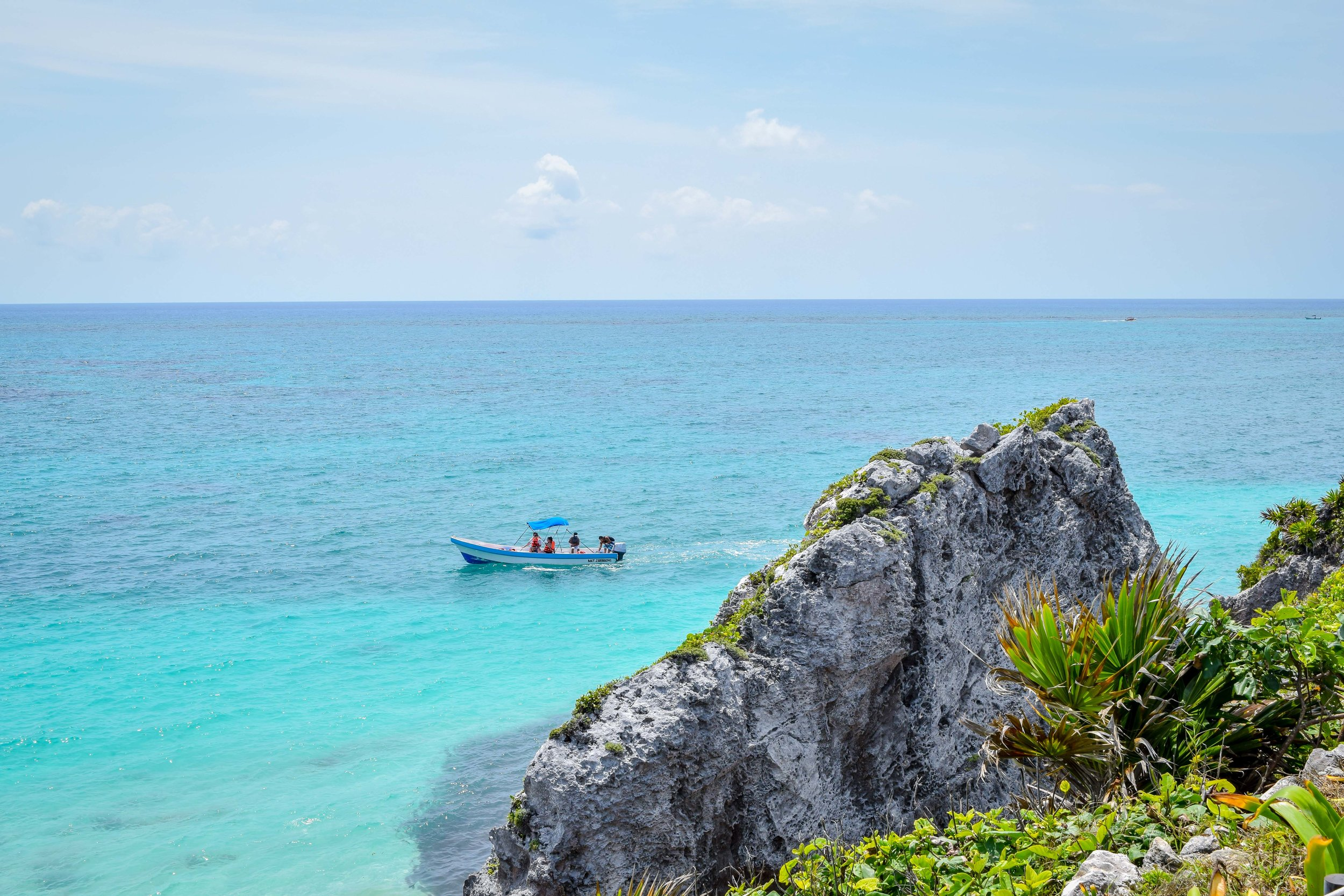 Turqoiuse waters and a boat off the coast of Tulum