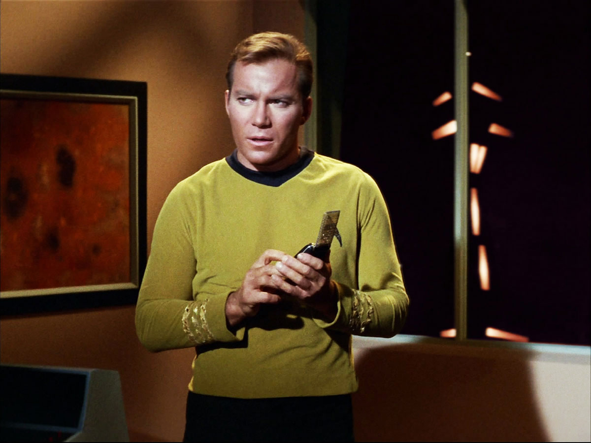 Captain James T. Kirk of the USS Enterprise (William Shatner) with a communicator, portable device allowing the crew members to exchange with each other, during ground missions, for example. Its derivative, the combadge, figuring the Starfleet emblem, will be worn, on the torso, by the crew members of Star Trek: The next generation, from 1987.