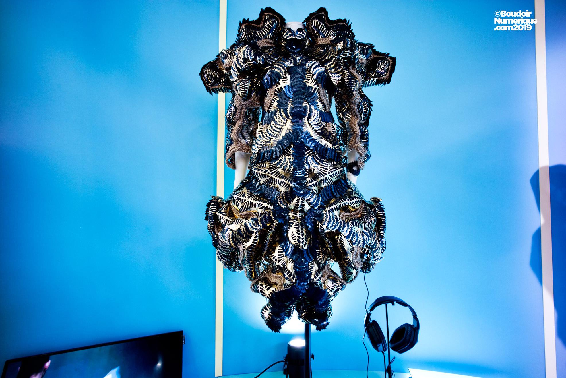 """Robe Interactive """"Spectral Radiance"""" de la designer hollandaise Maartje Dijkstra, créée en 2019, en collaboration avec Beorn Lebenstedt, connu sous son nom de DJ, Newk. Cette pièce unique, imprimée en 3D, intègre huit éléments qui réagissent à la musique imaginée par le musicien. Cette robe illustre la manière dont la musique influence le comportement humain."""