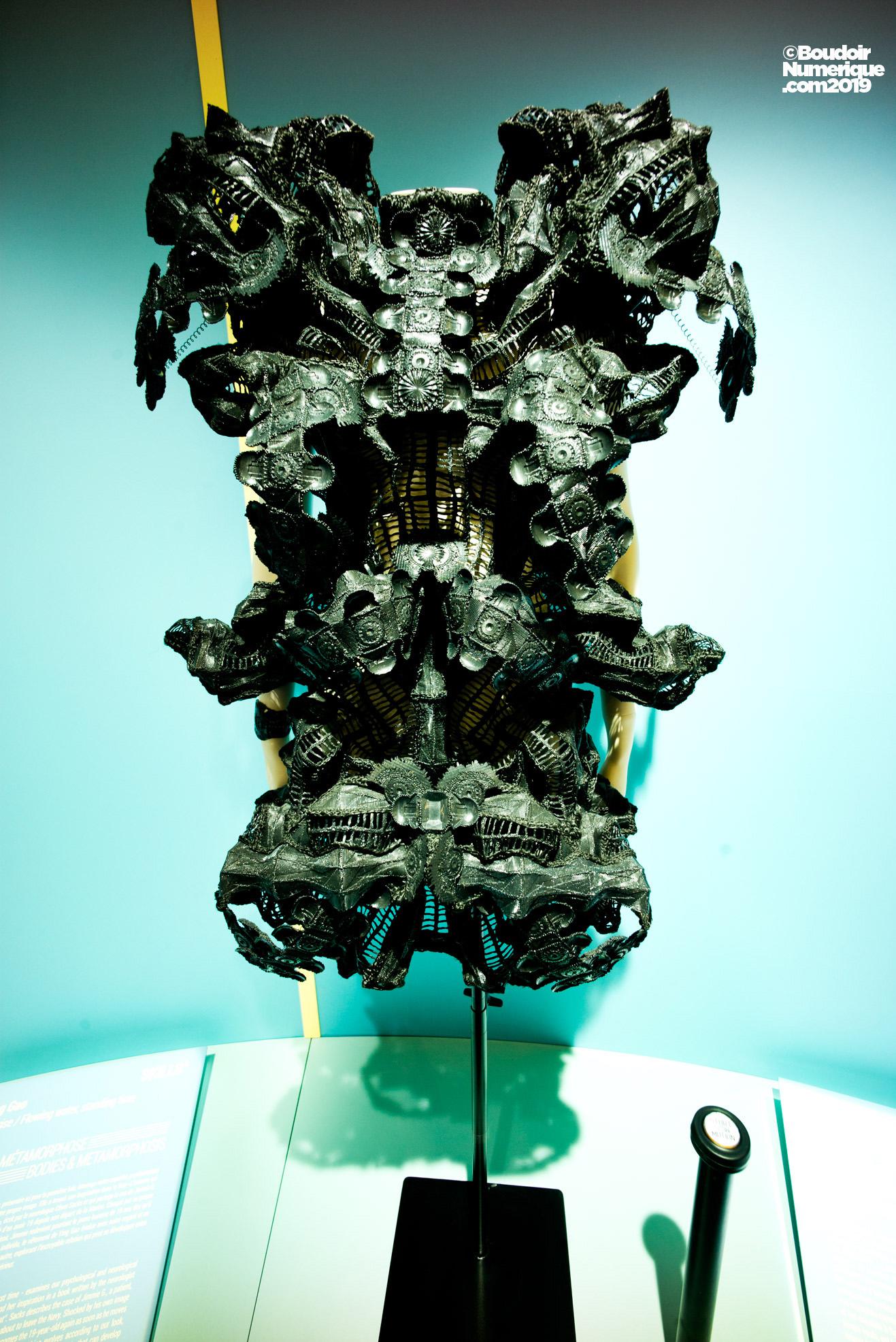 """Robe """"Suspended Animation"""" de la designer hollandaise Maartje Dijkstra, créée en 2019, en collaboration avec DJ Newk. La tenue évolue dans un mouvement extrêmement lent, avant de revenir à sa position originale, et cela afin de pousser à la réflexion sur l'hyper accélération de notre société technologique."""