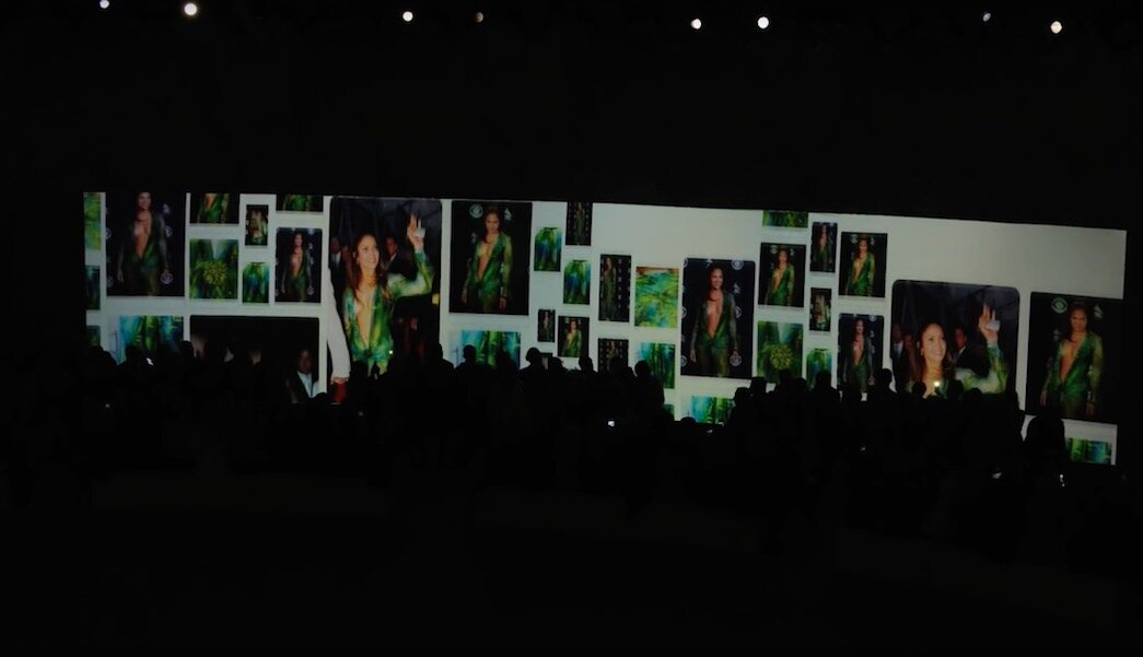 Défilé Versace printemps-été 2020, le 20 septembre 2019, à Milan, avec écran panoramique montrant les images de la jungle dress, portée par Jennifer Lopez, en 2000