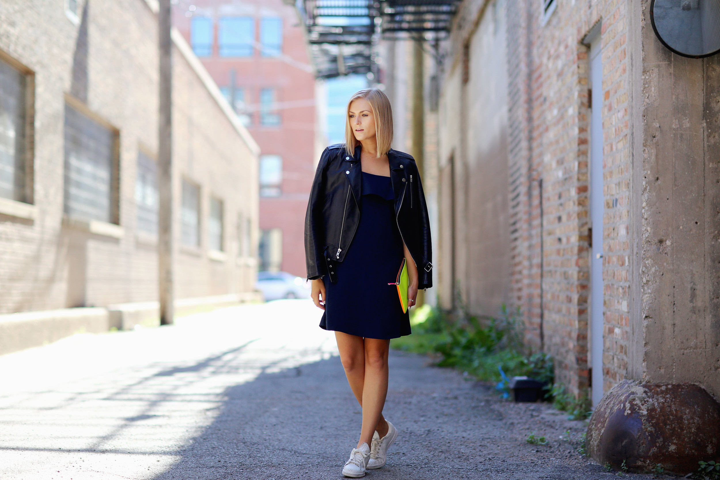 ali stone wears a slip dress with moto jacket and sneakers.jpg