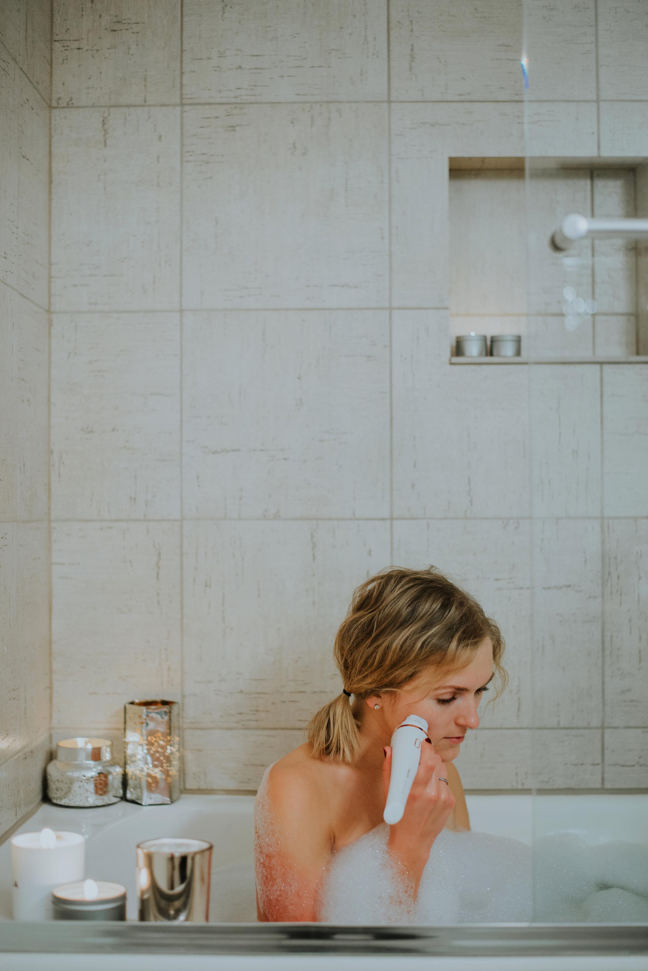 girl in bathtub exfoliating skin
