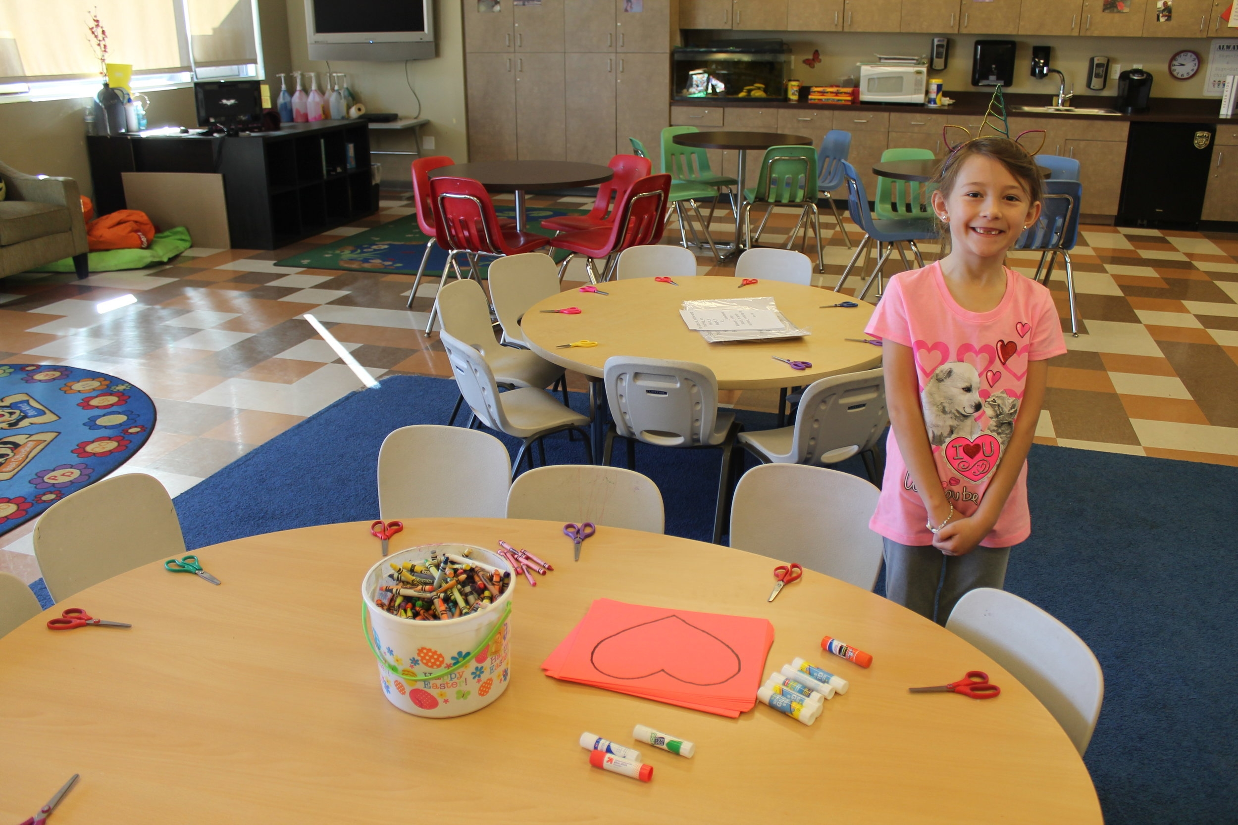 Abigail Allen, 7 year old volunteer, helped with the Valentine craft as she handed out the scissors, crayons, paste and red cut out hearts.